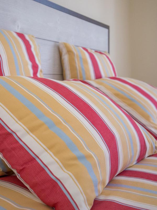 Oreillers aux couleurs orange, rouge, du lit de la chambre d'hôtes La Rochelle à Virson (17) près de Rochefort