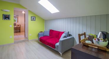 Une des trois chambres d'hôtes de charme à Virson (17) proche Rochefort : salon privatif avec canapé, pan de mur vert, une décoration de chambre en hommage à l'Île d'Aix.
