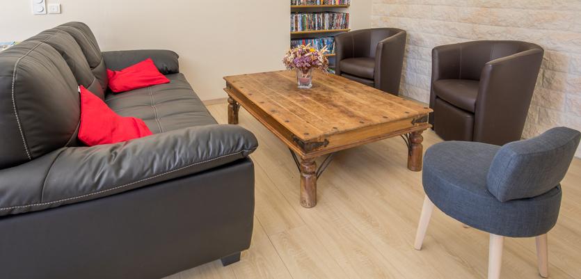 Partie commune de la maison d'hôtes Les Cagouilles à Virson (17) proche de Rochefort : coin salon avec table basse en bois, trois fauteuils, un canapé et une bibliothèque